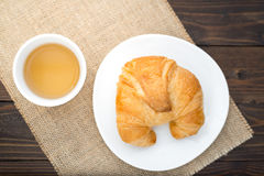 Fresh baked croissants with tea on napkin.  Royalty Free Stock Photos