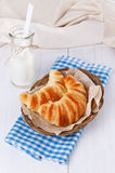 Fresh baked croissants on woven plate over white wooden backgrou. Fresh baked croissants on woven plate and bottle of milk over white wooden background stock photography