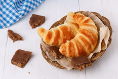 Fresh baked croissants on woven plate over white wooden backgrou. Fresh baked croissants on woven plate and pieces of fudge chocolate over white wooden stock photography