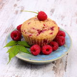 Fresh baked cupcake and raspberries on plate on old wooden background, delicious dessert Stock Image