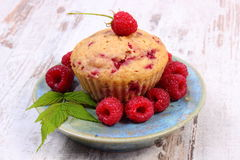 Fresh baked cupcake and raspberries on plate on old wooden background, delicious dessert Royalty Free Stock Images