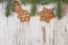 Fresh baked decorated gingerbread and spruce branches on old wooden background, christmas time Stock Photo
