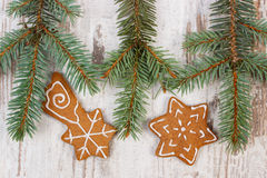 Fresh baked decorated gingerbread and spruce branches on old wooden background, Stock Images