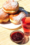 Fresh baked donuts with fruit jam and tea Stock Photography