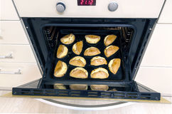 Fresh baked homemade cookies in oven. Tray of cookies coming out Royalty Free Stock Photography