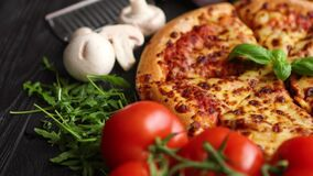 Fresh baked, hot american style pizza with all various ingredients on side stock video