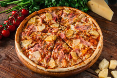 Fresh baked italian pizza served on wooden table. Delicious hawaiian pizza with ham and pineapple, served on rustic wooden background with cherry tomatoes Stock Photography