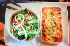 Fresh baked lasagna with vegetable salad. Close up Royalty Free Stock Photography