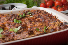 Fresh Baked Lasagne in Red Dish with Black Olives Tomatoes and Chilli on Wooden Table Royalty Free Stock Image