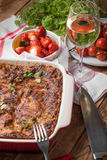 Fresh Baked Lasagne in Red Dish with Black Olives Tomatoes and Chilli on Wooden Table Royalty Free Stock Photo