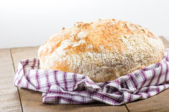 Fresh baked loaf of bread in cloth Royalty Free Stock Photo