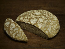 Fresh baked loaf of rye bread. Cut loaf of fresh baked rye bread on wooden background Stock Photography