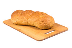 Fresh baked loaf on the wooden cutting board. Royalty Free Stock Images