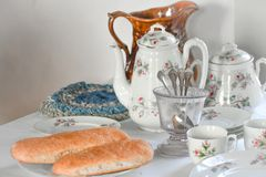 Fresh Baked Loaves of Bread on Table. A dining room table with a white tablecloth, tea cups, saucers, plates, tea pot, fresh baked bread, goblets and an old royalty free stock images