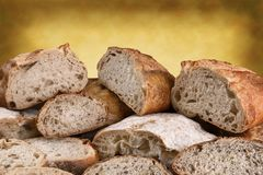 Fresh Baked Loaves of Bread Warm Background. A variety of fresh baked bread on a warm background, the loaves are cut in half and sliced royalty free stock photography