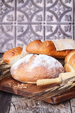 Fresh Baked Loaves of Breads. Variety of freshly baked breads and grain against a rustic background stock photo