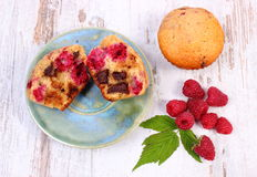 Fresh baked muffins with chocolate and raspberries on wooden background, delicious dessert. Homemade fresh baked muffins with chocolate and raspberries on old Stock Photography