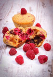 Fresh baked muffins with chocolate and raspberries on wooden background, delicious dessert Stock Photo