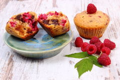 Fresh baked muffins with chocolate and raspberries on wooden background, delicious dessert. Homemade fresh baked muffins with chocolate and raspberries on old Royalty Free Stock Photos