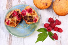 Fresh baked muffins with chocolate and raspberries on wooden background, delicious dessert. Homemade fresh baked muffins with chocolate and raspberries on old Royalty Free Stock Photo