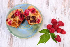 Fresh baked muffins with chocolate and raspberries on wooden background, delicious dessert. Homemade fresh baked muffins with chocolate and raspberries on old Stock Image
