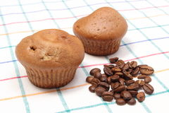 Fresh baked muffins and coffee grains on colorful cloth Stock Photography
