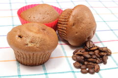 Fresh baked muffins and coffee grains on colorful cloth Stock Photos