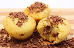 Fresh baked muffins and grated chocolate on wooden cutting board Stock Photography