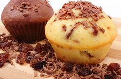 Fresh baked muffins and grated chocolate on wooden cutting board Stock Image
