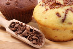 Fresh baked muffins and grated chocolate on wooden spoon Royalty Free Stock Images