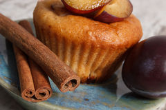 Fresh baked muffins with plums and cinnamon sticks on old wooden background, delicious dessert Royalty Free Stock Image