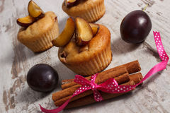 Fresh baked muffins with plums and cinnamon sticks on old wooden background, delicious dessert Stock Photo
