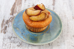 Fresh baked muffins with plums on plate on old wooden background, delicious dessert Royalty Free Stock Image
