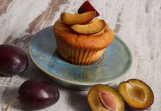 Fresh baked muffins with plums on plate on old wooden background, delicious dessert Stock Image