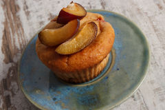 Fresh baked muffins with plums on plate on old wooden background, delicious dessert Royalty Free Stock Images