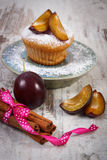Fresh baked muffins with plums and powdered sugar on plate, delicious dessert Stock Photos