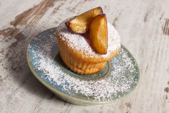 Fresh baked muffins with plums and powdered sugar on plate, delicious dessert Stock Photo