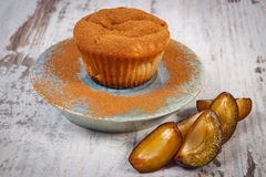 Fresh baked muffins with plums and powdery cinnamon on plate, delicious dessert Royalty Free Stock Images