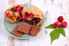 Fresh baked muffins with raspberries and chocolate on wooden background, delicious dessert. Homemade fresh baked muffins with raspberries and pieces of chocolate Royalty Free Stock Photography
