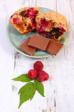 Fresh baked muffins with raspberries and chocolate on wooden background, delicious dessert. Homemade fresh baked muffins with raspberries and pieces of chocolate Stock Photos