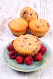 Fresh baked muffins with raspberries on old wooden background, delicious dessert. Homemade fresh baked muffins with raspberries on old rustic wooden background Stock Photos