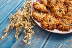 Fresh baked oatmeal cookies and ears of oat, healthy dessert concept Stock Photos