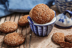 Fresh baked oatmeal cookies with sesame seeds in a cup. Sesame c Stock Photos