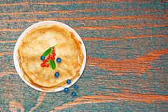 Fresh baked pancakes on white plate on wooden table grunge, retro style, close-up, top view, Royalty Free Stock Images