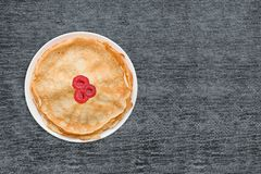 Fresh baked pancakes on white plate on wooden table grunge, retro style, close-up, top view, Royalty Free Stock Photography
