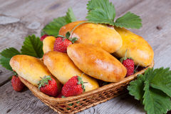 Fresh baked pasties with strawberries in a basket close-up. Fresh baked pasties with strawberries in a basket Stock Photo