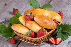 Fresh baked pasties with strawberries in a basket close-up. Fresh baked pasties with strawberries in a basket Royalty Free Stock Image