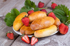 Fresh baked pasties with strawberries on plate close-up. Fresh baked pasties with strawberries on plate Royalty Free Stock Photography
