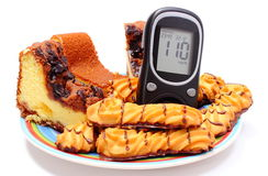 Fresh baked pastry and glucose meter. White background Stock Image