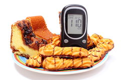 Fresh baked pastry and glucose meter. White background Royalty Free Stock Photo